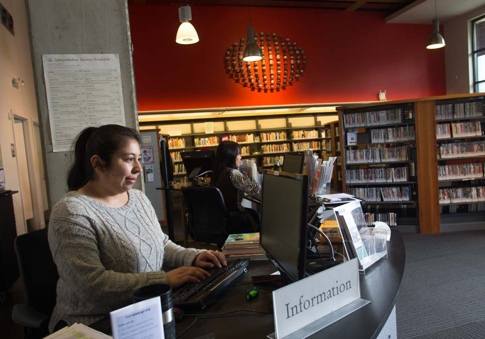Library staff at the service desk area at the International District/Chinatown Branch
