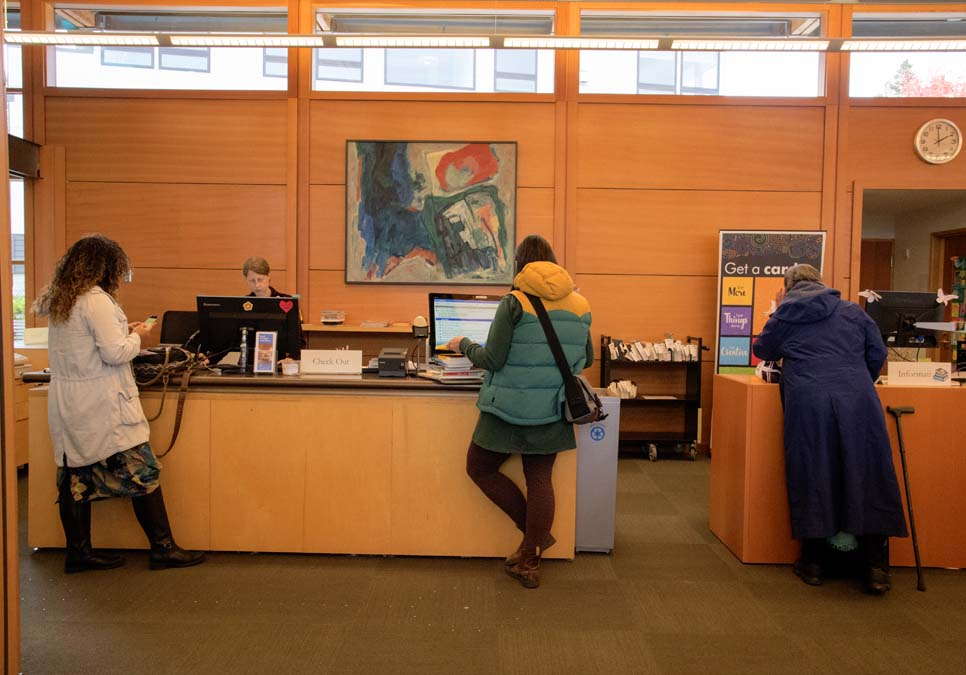 Library patrons at the service desk area at the Montlake Branch